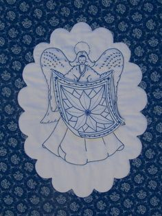 """Redwork embroidery pattrn. # 40 """"The Quilting Angel"""". She hold a quilt hanging loose from her hands. Apprvimately 15"""" x 20'. Available on my website for 9.00. www.quiltingbeedesigns.com"""