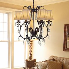 Give any room a luxurious upgrade with this beautiful wrought iron chandelier from Versailles. Featuring six lights with silk shades, crystal accents, and a a black finish, this traditional light fixture will bathe your room in light and style.