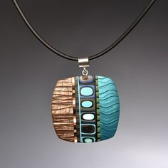 Meisha Barbee, polymer clay pendant made using a mica shift technique as a background to canes.