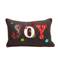 This handcrafted accent pillow features a houndstooth cover with hand-cut Patterned applique patchwork that spells out 'Joy' for a festive, stylish accent perfect tossed on to a bed, sofa, chair or wi