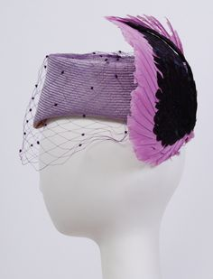 Jack McConnell straw and feather hat (side view) | Trimmed with purple netting and decorated with two toned mauve and iridescent purple feather wings | United States, 1980's