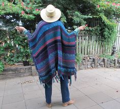 Ways to get noticed. Boho Hip rectangular poncho, This one uses a variety of yarns with different textures, but is the color of a peacock feather! All blues, purples and Aqua greens - and a touch of pink / apricot for good measure!  Great for heading out to a festival, or any time when its a lil cool  Fringed around the sides and bottom edges of the shawl  One size suits pretty well everyone really, the model wearing this one is 59 or around 175cm, so someone around 5.5, the length would...