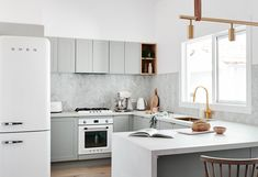 The norsuHOME - Kitchen  Photographer: Lisa Cohen Stylist: Beck Simon  Paint: Dulux Vivid White Tiles: Perini Tiles Cabinetry: kaboodle Kitchens Flooring: Godfrey Hirst  Benchtop: Caesarstone Appliances: Smeg Tapware: Sussex Taps Sink: ABI Interiors  Products: GlobeWest Sketch Requin Barstools, Rubn Long John Brass and Leather strap pendant, Menu Grinders (all available at www.norsu.com.au)