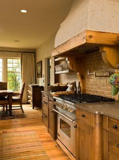 The Heart of a Home: Creating a Warm Kitchen. Hood, swinging water tap, brick backsplash, curved counter edges.