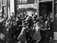 Children rush into a candy store at the end of the British Sweet Ration of 1953