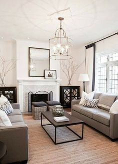 White painted living room with soft grey furniture and natural coloured floorboards. Stunning light fitting!