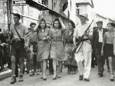 Two young women who collaborated with the Germans are escorted by French Resistance (FFI). June 1944. The women are touching their hair which will soon be cut. The FFI member on the right wears a hand grenade in his belt as well as the French flag emblem on the sleeve of his shirt. Southern France, 1944.