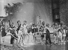 Children playing in a fire hose in depression-era Minnesota.