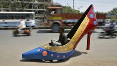 In der südindischen Stadt Hyderabad fährt ein Mann mit einem motorisierten High Heel des Autodesigners Sudhakar Yadav. Das Gefährt, das maximal 45 Stundenkilometer fahren kann, ist Teil einer Serie von Autos, die er aus Anlass des Weltfrauentags geschaffen hat.  www.sz.de/1.1297863-168