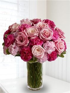 A beautiful bouquet of flowers that includes pink roses and hot pink carnations