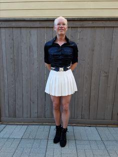 White pleated bcbg skirt, black satin silk bebe shirt, nude nylons, black chunk high heeled shoes.