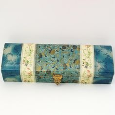 """Celluloid glove box. The flower motif covers the box in blues, golds, white and pinks. The box measures 12 ½"""" x 4"""" x 2""""."""