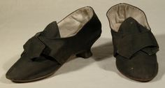 Shoes, 1780-1790, England, Leather, Linen, Wool. Made of black woven wool and covered heel. Brown leather sole. Blunt point toe. Italian heel covered and shaped. Top piece leather. Sole shaped, worn and continues to heel breast. Polish sides at waist. Upper - vamp extends to pointed tongue. Side seam slanted forwards, open slits, quarters extend to latchets. Lining is white linen with white linen sock. Writing on vamp 'Miss Molly'.