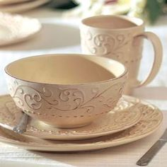 """Sixteen-piece dinnerware set with scrolling detail.   Product: (4) 10.75"""" Dinner plates(4 ) 8.25"""" Salad plates(4 ) 6.5"""" Bowls(4) 4"""" Mugs  Construction Material: Earthenware  Color: Cream     Features: 14 Ounce capacity (mug)      Cleaning and Care: Dishwasher safe"""