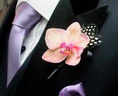 Dainty pink orchid and spotted feather boutonnière for a groom