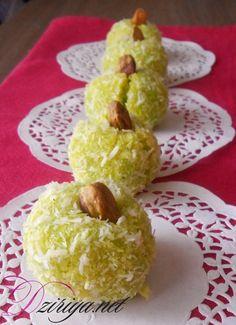 Dans un saladier, mélangez 180 g de noix de coco, le sucre, la poudre de pistache, le zeste de citron et l'extrait de pistache. Ajoutez les oeufs puis mélangez. Vous devez obtenir une boule de pâte. Ajoutez le colorant vert puis mélangez pour l'imprégner à la pâte. Réalisez des petites boules de la taille d'une noix puis enrobez-les dans la noix de coco. Piquez le centre des Mchewek d'une pistache pour décorer. Déposez vos petits fours sur une plaque allant au four et enfourner pour 10 mi...