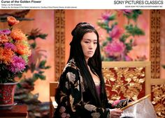 Gong Li as the Empress in Curse of the Golden flower. black embroidered dress. side view.