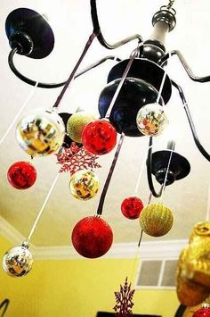 Hang ornaments from a light fixture to transform it into a Christmas chandelier. | 38 Clever Christmas Hacks That Will Make Your Life Easier