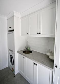 LAUNDRY IDEAS - We custom designed and manufactured this laundry, with 'shaker' profile doors, a marble inspired stone benchtop. Finished off with a white tiled splashback and black handles and knobs.   #kitchensbyemanuel #kbecastlehill #laundry #laundryideas #laundrygoals #laundryinspo #customdesignedlaundry #customlaundry #sydney #local #custombuiltlaundry