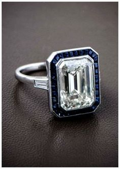 A gorgeous emerald cut diamond surrounded by a halo of Ceylon sapphires and set in a beautiful platinum mounting. Such a wonderful antique engagement ring!