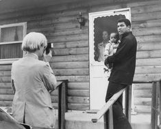 Pop Artist Andy Warhol, Left, Is Shown Photographing Muhammad Ali, His Infant Daughter, Hanna, And Wife, Veronica, Thursday, August 18, 1977, At Ali's Training Camp In Deer Lake, Pa