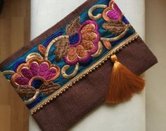 Floral Clutch, Ethnic Clutch Bag, Bohemian Clutch, Ethnic Handbag, Womens Bag, Handmade Gift, Summer Finds, Gift for her, Bridal clutch  A fashion statement that everyone will swoon over! This floral clutch will bring elegance to your style. It will be chic with jeans or dresses and you may use this clutch bag both day and night. This clutch bag is perfectly handmade with high quality mustard yellow jute fabric. Designed with a silk bohemian embroidery and a tassel. Clutch has a silk satin…