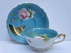 Two beautiful sets of Japanese porcelain teacups and saucers One set is pale blue, and the other one dark blue Beautiful hand painted roses and gold butterflies ar on blue background Raised golden borders on each piece Cups and saucers have a wavy edge The outside of the cups is painted