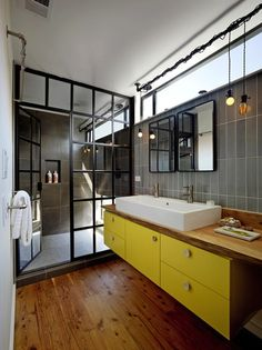 I love this picture because of the shapes in the shower, it gives it an industrial look especially together with the lights. The pop of colour on the cabinets makes it feel more modern and stylish.