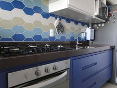 Now that's a bright kitchen splash back! Blue, white, natural - hexagon tiles in a patterned wall. Tiles are Portobello Chez Moi range.