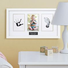 """Capture your little one's tiny hand and footprint impression in this classic white wood frame. There's a window for baby's 6""""L x 4""""W photo in the center. Frame measures 12""""L x 18-1/2""""W comes complete with a white beveled mat and mess-free """"clean-touch"""" ink pad. We personalize it with any name and any date, up to 24 characters each. For wall mount."""