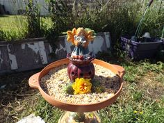 an old lamp base, with a clear vase with dried flowers in it, topped by a pottery birdfeeder base, with a ceramic angel added, and a solar light to the back.
