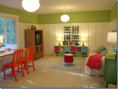 Like the tall paneling with hit of color on top, love the orange chairs!