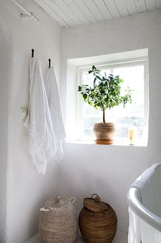 Rattan baskets in a crisp white bathroom give texture in a clean space