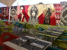 Wynwood Kitchen and Bar, Miami - This visually striking restaurant presents artwork by talented artists from the city's urban street-art scene to go along with its innovative small plates by chef Miguel Aguilar, formerly of Alma de Cuba. The Arts District hotspot's exterior is swathed in murals by twin Brazilian artists Os Gemeos. Other works include pieces by American collaborative Dearraindrop, well-known artist Kenny Scharf, and acclaimed graffiti artist Shepard Fairey. As for the dining…