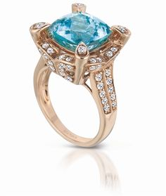 18k Strawberry Gold® high profile ring is studded with 1.16 cts. t.w. of Vanilla Diamonds and centered with a 7.19 ct. cushion-cut Neon Blue Paraiba Tourmaline®.    Le Vian Couture