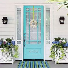 Aqua door flanked by square planters.