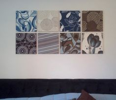 """DIY wall art.  Less than $30!   18x18"""" sample pieces of discontinued patterns at Joann fabrics wrapped around 12"""" canvases from Michaels. Look for the bulk packs.  Easy to hang with those amazing 3M command strips. Use the picture hanger style.  They're 2 pieces that velcro and they'll clear the bulk of the fabric.  Your panels will lay flat nicely againt the wall."""