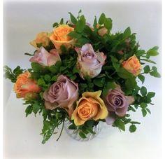 Vakker rosebukett med roser i lekre sommerlige farger sammen med sommerens og sesongens lyng i grønt