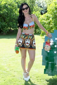 Katy Perry in a Dolce & Gabbana cropped top and matching skirt at the Lacoste pool party. She accessorized with a vintage Lulu Guinness bag.