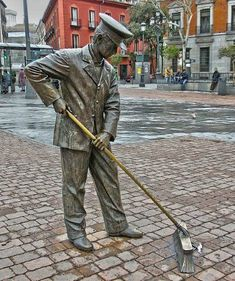 Sculpture of a man sweeping the street.