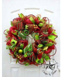 This wreath is created using red and lime wide foiled mesh along with various ribbons in coordinating colors. The final addiction is the glamour roping and present.