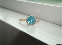 A PenelliBelle, Inc. ring with a rose gold band, an aqua apatite gemstone and a halo of diamonds. So pretty