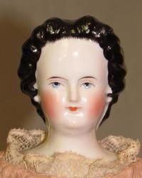 Antique china doll with molded bun and snood.