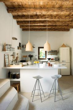 In a quiet corner of the famed Spanish party island, rug designer Nani Marquina and photographer Albert Font have carved out a serene, site-sensitive home. Jamaica barstools by Pepe Cortès for Knoll and two Ikea pendants pair nicely with the plaster walls, restored wooden beam ceilings, and polished cement floors in the kitchen