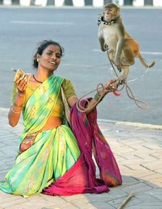 An unidentified nomadic indian woman jolts her performing monkey into action in a performance for passersby on a street in Mumbai. Street performers are a common sight in Indian cities.