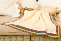 Knitted baby blanket with striped border. Shop the knitting pattern at The Knitting Network now