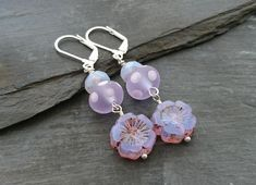 These pretty earrings have been made with Czech glass beads; one rondelle and one flower. A polka dot lamp work bead sits between them. They've been attached to silver plated lever back ear wires, to give a little extra security. Mauve, Lilac, Purple, Handmade Jewellery, Earrings Handmade, Flower Earrings, Drop Earrings, Czech Glass Beads, Wire