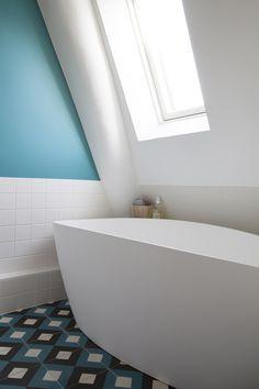 Le bleu du mur se retrouve sur les carreaux de ciments à motif du sol de la salle de bain / Archi : ATELIER PREMIER ETAGE