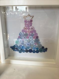 Button framed Art. Beautiful dress - buttons glued onto card and framed with the addition of a few little gems creates a beautiful artwork. Created by an 11 year old. #art #buttons #frame #kids #kidscraft #craft #buttonart