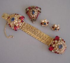 HOBE red, clear and blue  bracelet, brooch and earrings with patriotic  colored rhinestones set into gold tone filigree,  patent number 143,317  circa  1945, bracelet 7, brooch 1-3/4 by 1-1/2,  earrings 1. The stones are brilliant and unfoiled and the  bracelet an unusual front-opening style.